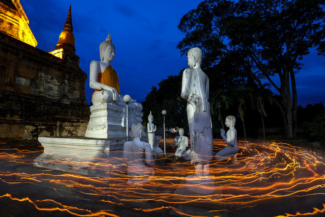 Buddhists carry candles as they pray during Vesak Day, an annual celebration of Buddha's birth, enlightenment and death, at Wat Yai Chai Mongkhon temple in Ayutthaya, Thailand on May 10, 2017. (Photo by Athit Perawongmetha/Reuters)