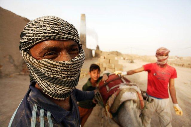 Iraqi men work at a brick factory near the central Iraqi shrine city of Najaf on May 16, 2017. (Photo by Haidar Hamdani/AFP Photo)