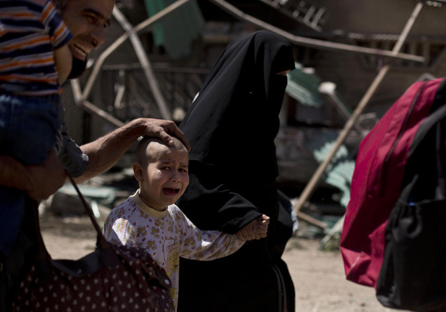 A girl with a shaved head and her father cry as the family flees the al-Refai neighborhood while Iraqi special forces battle Islamic State militants in western Mosul, Iraq, Wednesday, May 17, 2017. (Photo by Maya Alleruzzo/AP Photo)