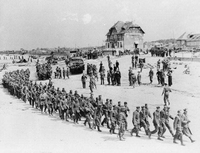 German prisoners-of-war march along Juno Beach landing area to a ship taking them to England, after they were captured by Canadian troops at Bernieres Sur Mer, France, June 6, 1944. REUTERS/Ken Bell/National Archives of Canada