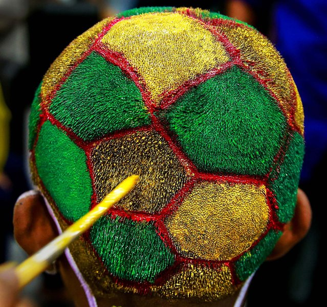 A boy gets his head painted as part of a promotional event ahead of the World Cup at a saloon in Mumbai, India, June 9, 2014. (Photo by Rafiq Maqbool/Associated Press)