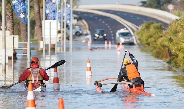 Two men paddle their kayaks through a flooded road in Palavas-les-Flots following overnight storm in southern France, on November 23, 2019. (Photo by Pascal Guyot/AFP Photo)