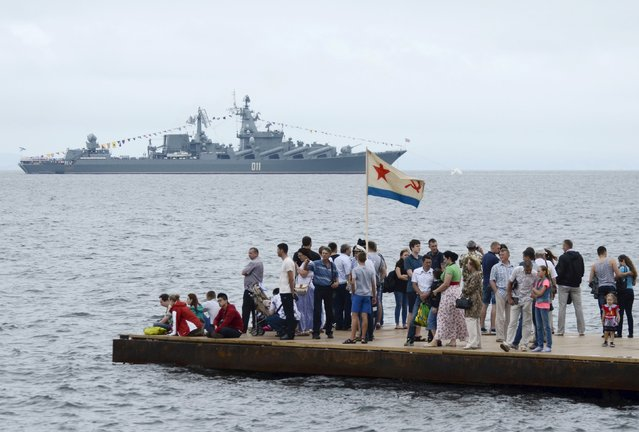 People gather to watch celebrations for Navy Day, with a Russian warship seen in the background, in the far eastern city of Vladivostok, Russia, July 26, 2015. (Photo by Yuri Maltsev/Reuters)