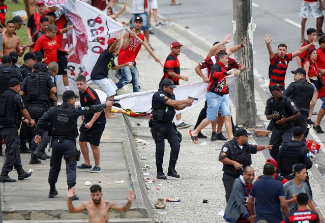 Riot police disperse fans of Flamengo football club taking part in a celebration parade, following the team's arrival from the Libertadores final, after some alleged theft incidents within the crowd, in Rio de Janeiro, Brazil on November 24, 2019. (Photo by Ueslei Marcelino/Reuters)
