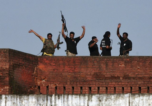 Indian security personnel celebrate on the roof of a police station after a gunfight in Dinanagar town, in Gurdaspur district of Punjab, India, July 27, 2015. Indian police overcame a group of gunmen dressed in military fatigues on Monday after a 12-hour battle that ended in the small-town police station near the border with Pakistan, and at least nine people were killed. (Photo by Munish Sharma/Reuters)