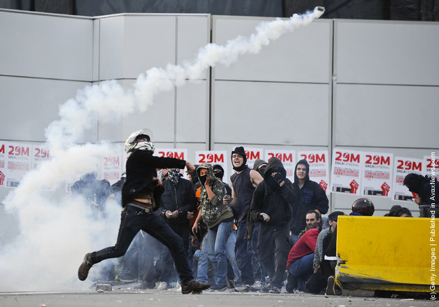 A demonstrator throws back a teargas canister during heavy clashes with riot police during a 24-hour strike on March 29, 2012 in Barcelona, Spain