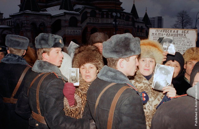 Soviet mothers who lost their sons in the Red Army are held back by State militia as they hold photographs of their loved ones in Red Square, on Monday, December 24, 1990. A group of about 200 Soviet parents who have all lost sons through ethnic violence and accidents within the Soviet armed services demonstrated outside the Kremlin. 6,000 Soviet service men were killed during 1990