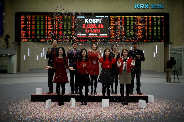 Employees of the Korea Exchange (KRX) pose in front of the final stock price index during a photo opportunity for the media at the ceremonial closing event of the 2016 stock market in Seoul, South Korea, December 29, 2016. (Photo by Kim Hong-Ji/Reuters)