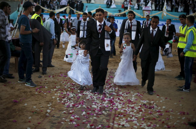 Palestinian girls accompany grooms as they walk separate from the brides during a mass wedding for 150 couples in Beit Lahiya town in the northern Gaza Strip July 20, 2015. (Photo by Suhaib Salem/Reuters)