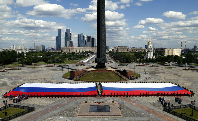 """Cadets of the high school of the Russian Emergencies Ministry hold what is said to be the largest flag of Russia, at the Poklonnaya hill, marking the upcoming """"Day of Russia"""" celebration, in Moscow, Russia, 10 June 2016. The flag measures some 2,100 square meters, according to the Russian Emergencies Ministry. Since 1992 the """"Day of Russia"""" is annually celebrated on 12 June as the Russian Federation's national holiday. (Photo by Maxim Shipenkov/EPA)"""