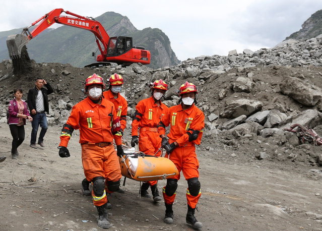 Rescue workers carry a victim at the site of a landslide that occurred in Xinmo Village, Mao County, Sichuan province, China, June 25, 2017. (Photo by Reuters/China Daily)