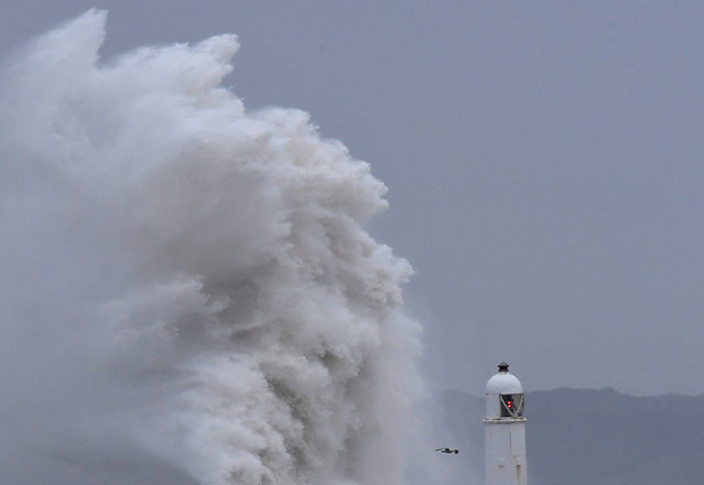 People watch as large waves crash against the seawall during strong winds at Porthcawl, Britain, March 16, 2019. (Photo by Toby Melville/Reuters)
