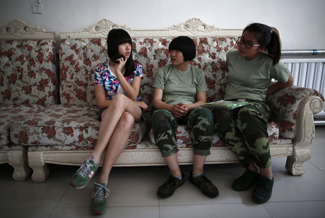 A girl who has just been taken to the Qide Education Center (L), at the request of her parents, speaks to other participants on the course in Beijing May 22, 2014. (Photo by Kim Kyung-Hoon/Reuters)