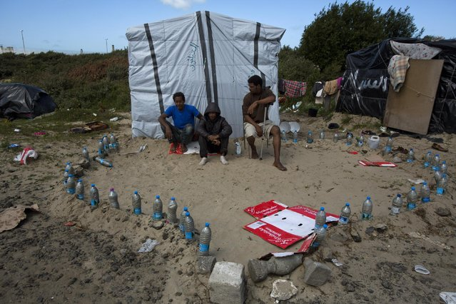 Migrants sit at an improvised mosque at a camp set near Calais, northern France, Tuesday, August 4, 2015. (Photo by Emilio Morenatti/AP Photo)