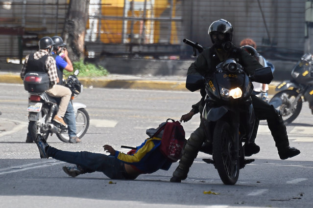 Members of the National Guard arrest an opposition activist during a demonstration against the government of Venezuelan President Nicolas Maduro, in Caracas on June 26, 2017. A political and economic crisis in the oil-producing country has spawned often violent demonstrations by protesters demanding Maduro's resignation and new elections. The unrest has left 75 people dead since April 1. (Photo by Juan Barreto/AFP Photo)