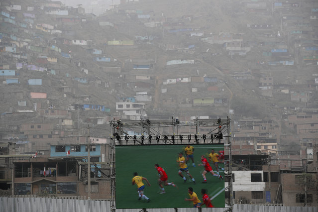 A screen shows action replay of a rugby seven match between Canada and Brazil during the Pan American Games inside a stadium where homes can be seen on the hillside behind in Lima, Peru, Sunday, July 28, 2019. (Photo by Moises Castillo/AP Photo)