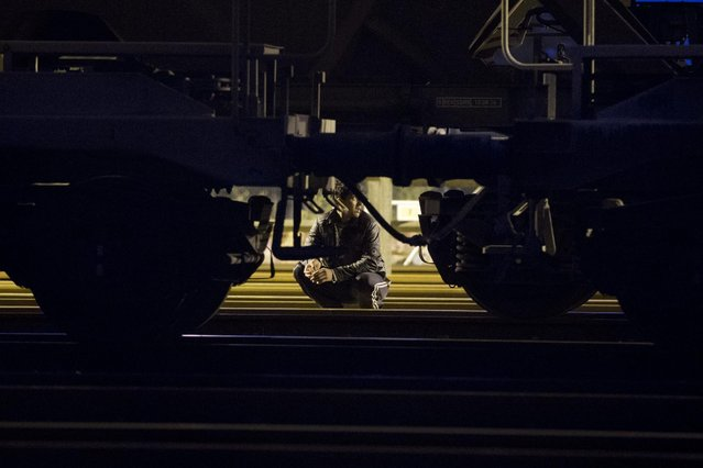 A migrant sits hides behind a train as he attempts to access the Channel Tunnel in Calais, northern France, Wednesday, August 5, 2015. Thousands of migrants have been scaling fences near the Channel Tunnel linking the two countries and boarding freight trains or trucks destined for Britain. (Photo by Emilio Morenatti/AP Photo)