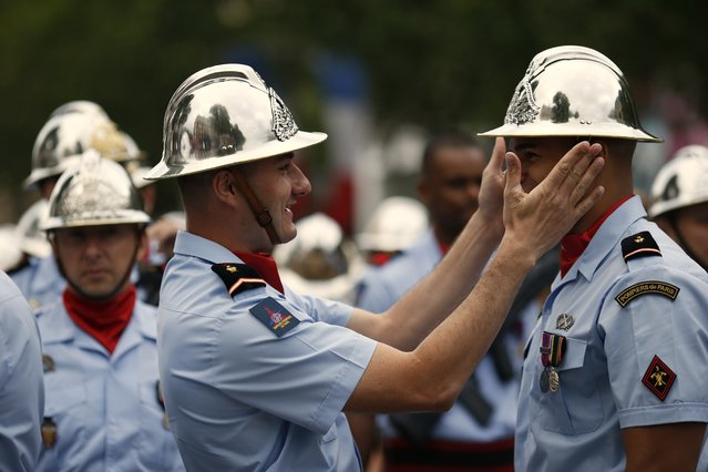 Parisian firefighters prepare their uniforms prior to the start of the annual Bastille Day military parade in Paris, on July 14, 2014. (Photo by Kenzo Tribouillard/AFP Photo)