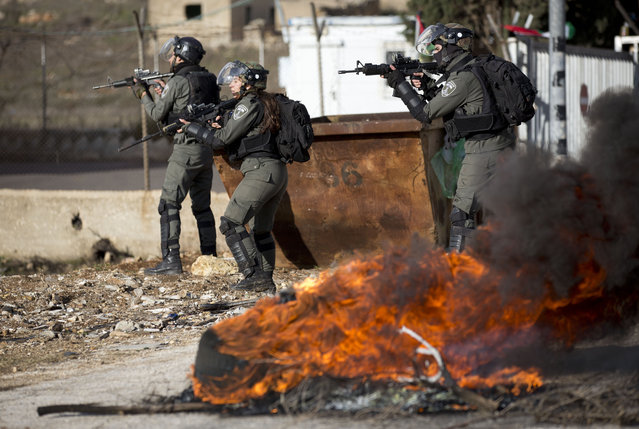 Israeli troops take their position during clashes with Palestinian demonstrators as they protest Middle East peace plan announced Tuesday by US President Donald Trump, which strongly favors Israel, at Beit El checkpoint, near the West Bank city of Ramallah, Wednesday, January 29, 2020. (Photo by Majdi Mohammed/AP Photo)