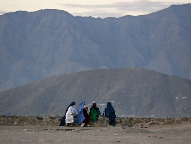 Afghan women look down at part of the city from a hill top in the early morning hours in Kabul, Afghanistan July 30, 2015. (Photo by Ahmad Masood/Reuters)