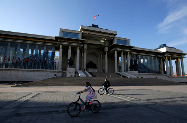 People cycle past the parliament building at Genghis Square in Ulaanbaatar, Mongolia, June 27, 2016. (Photo by Jason Lee/Reuters)