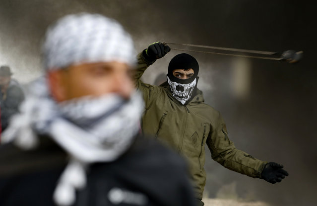 A Palestinian protester uses a slingshot during a demonstration against a US-brokered peace proposal, in the occupied West Bank village of Bilin near Ramallah on February 7, 2020. Israel deployed additional forces in Jerusalem and the occupied West Bank ahead of weekly Muslim Friday prayers, a day after a deadly uptick in violence. The rise in violence comes a week after US President Donald Trump released a long-delayed plan for the Middle East that angered the Palestinians. (Photo by Abbas Momani/AFP Photo)