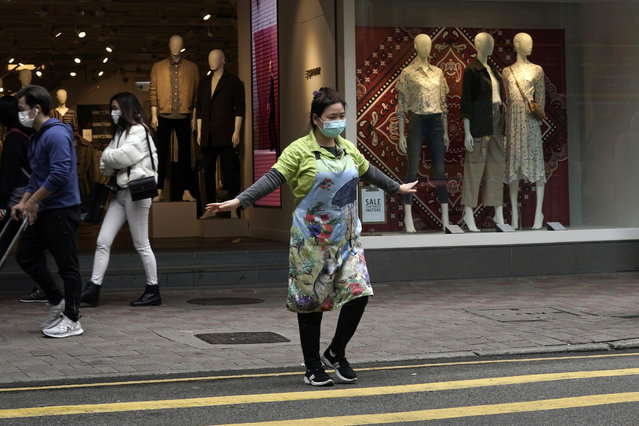A woman wearing masks, stretches her arms in Hong Kong, Wednesday, February 19, 2020. Russia says it will temporarily ban Chinese nationals from entering the country amid the outbreak of the new virus centered in China that has infected more than 73,000 people. (Photo by Kin Cheung/AP Photo)