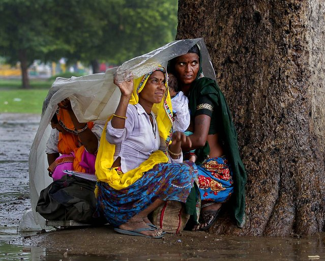 Women sit under a plastic sheet to shelter themselves from the rain in New Delhi, India on July 12, 2012