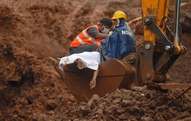 In this Thursday, July 31, 2014 photo, the limp hands of a victim hang as rescuers recover the body from the site of a landslide in Malin village, in the western Indian state of Maharashtra. Heavy rains hampered efforts Friday by hundreds of rescue workers digging through heavy mud and debris, as the death toll from a landslide that engulfed an entire village in western India crossed 50. (Photo by Nitin Lawate/AP Photo)