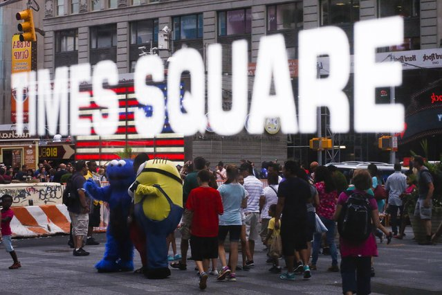 """A person dressed as the Sesame Street character Cookie Monster (L) and """"Minion"""" from the """"Despicable Me"""" movie are reflected in a window as they attempt to attract customers to pose for photos and tips in Times Square in New York July 29, 2014. (Photo by Eduardo Munoz/Reuters)"""
