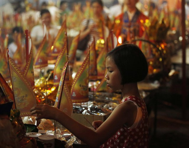 A child decorates food offerings at the Hungry Ghost festival in Kuala Lumpur August 3, 2014. According to Taoist and Buddhist beliefs, the seventh month of the Chinese Lunar calendar, known as the Hungry Ghost Festival is when the Gates of Hell open to let out spirits who wander the land of the living looking for food. Food offerings are made while paper money and joss sticks are burnt to keep the spirits of dead ancestors happy and to bring good luck. (Photo by Olivia Harris/Reuters)