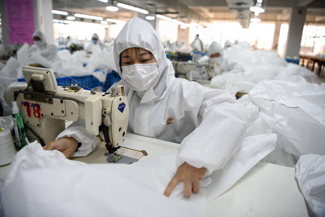 Workers sew hazardous material suits to be used in the COVID-19 coronavirus outbreak at the Zhejiang Ugly Duck Industry garment factory in Wenzhou on February 28, 2020. The number of new cases of the COVID-19 coronavirus in China has declined in recent days, but infections in other countries have gathered pace. (Photo by Noel Celis/AFP Photo)