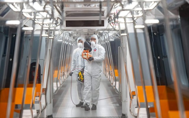 Employees of the Istanbul Municipality wearing protective gear disinfects a subway carriage to prevent the spread of the COVID-19, caused by the novel coronavirus, in Istanbul on March 12, 2020. Turkey announced on March 11, 2020 its first coronavirus case, a man who had recently travelled to Europe and is in good health. Turkey has announced several measures in recent weeks to try and stop the virus reaching the country, including thermal cameras at airports, cancelling flights to affected countries and closing its border with Iran. (Photo by Yasin Akgul/AFP Photo)