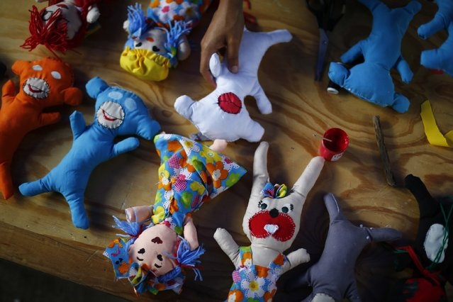 Puppets, which were hand-made to welcome Gaza's children, are seen lined along a table in Caracas, August 9, 2014. As violence rages on in the Gaza Strip, Venezuelan craftspeople gathered Saturday in Caracas to fashion hand-made toys for Gazan children. Dozens of adults and children participated in the toymaking, which was led by local artesans specialising in typical Venezuelan toys, including colourful spinning tops and cloth dolls. (Photo by Jorge Silva/Reuters)