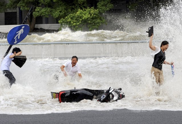 Visitors fall as they are hit by a wave caused by a tidal bore which surged past a barrier on the banks of Qiantang River, in Hangzhou, Zhejiang province August 14, 2014. (Photo by Reuters/Stringer)