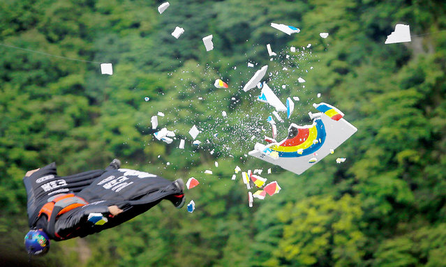 Wingsuit flyer Zhang Shupeng of China hits the target during the 6th Carabao World Wingsuit Championship at Tianmen Mountain on Sepember 8, 2017 near Zhangjiajie, Hunan province, China. A total of 16 participants from around the world take part in the extreme sport which involves jumping down cliffs at an altitude of 1,458 m (4,783,000 ft) while wearing a wingsuit. (Photo by Wang He/Getty Images)