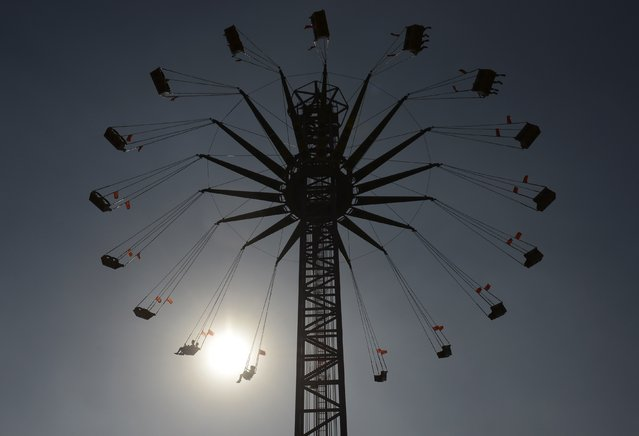 People sit on a ride at an amusement park as the sun sets behind them in Taiyuan, Shanxi province July 30, 2014. Picture taken July 30, 2014. (Photo by Jon Woo/Reuters)