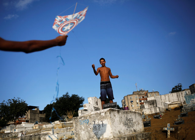 A man (L) helps his friend to fly a kite in a cemetery in the Vila Operaria Favela of Rio de Janeiro, Brazil, June 25, 2016. (Photo by Nacho Doce/Reuters)