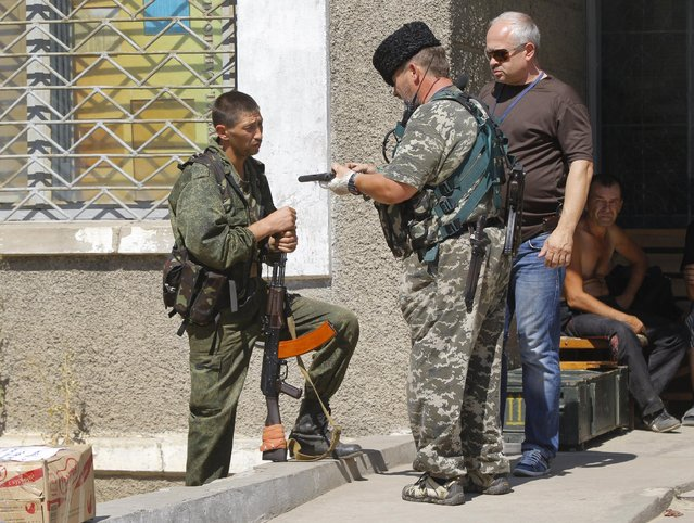 Pro-Russian rebels converse on a street in the town of Krasnodon, eastern Ukraine, Friday, August 15, 2014. (Photo by Sergei Grits/AP Photo)