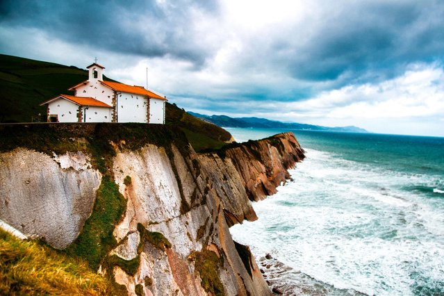 """""""I would do anything to go back to the beautiful moment and view"""", wrote Margaret Elise Wroblewski, 21, of Olney, Md., who took this photo in Zumaia, Spain. The atmosphere lit up the church """"perfectly against the texture of the cliffs"""". (Photo by Margaret Elise Wroblewski)"""
