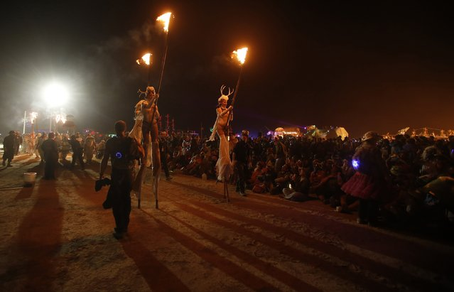 "The procession is seen before the Man burns during the Burning Man 2014 ""Caravansary"" arts and music festival in the Black Rock Desert of Nevada, August 30, 2014. (Photo by Jim Urquhart/Reuters)"