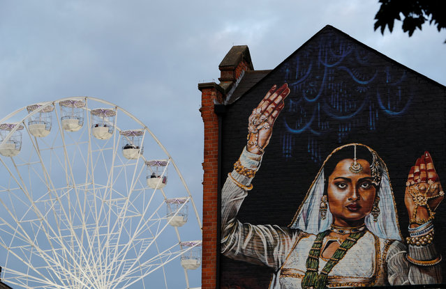 People ride on a ferris wheel behind a giant mural during the Diwali lights switch on in Leicester, Britain October 8, 2017. (Photo by Darren Staples/Reuters)