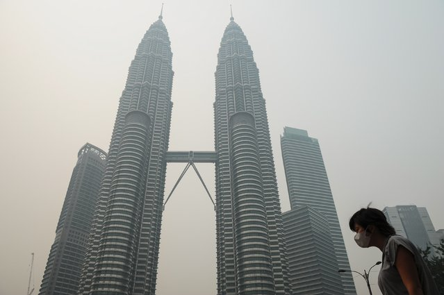A woman wears a face mask as Malaysia's iconic Petronas Twin Towers (back) are seen shrouded by haze in Kuala Lumpur on September 11, 2015. The thick haze came from blazes on western Sumatra island and the Indonesian part of Borneo island, which are home to huge palm oil and pulp and paper plantations. (Photo by Mohd Rasfan/AFP Photo)
