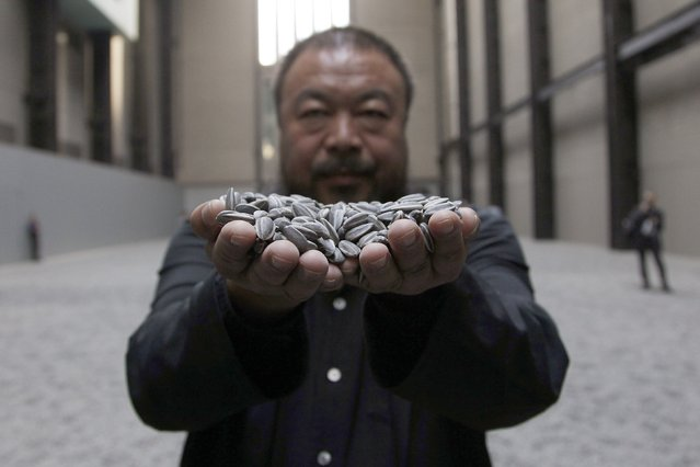 """Chinese artist Ai Weiwei poses for a photograph with his installation entitled """"Sunflower Seeds"""", at its unveiling in the Turbine Hall at the Tate Modern gallery, in London October 11, 2010. (Photo by Stefan Wermuth/Reuters)"""