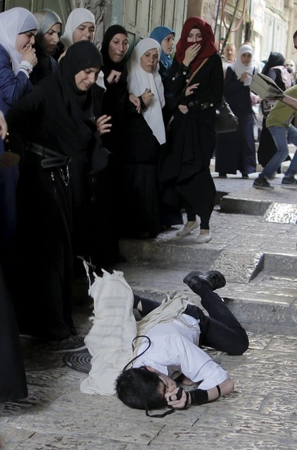 Palestinian women look on as an Orthodox Jew lays on the floor after he was attacked by other Palestinians during clashes in Jerusalem's Old City September 13, 2015. (Photo by Ammar Awad/Reuters)