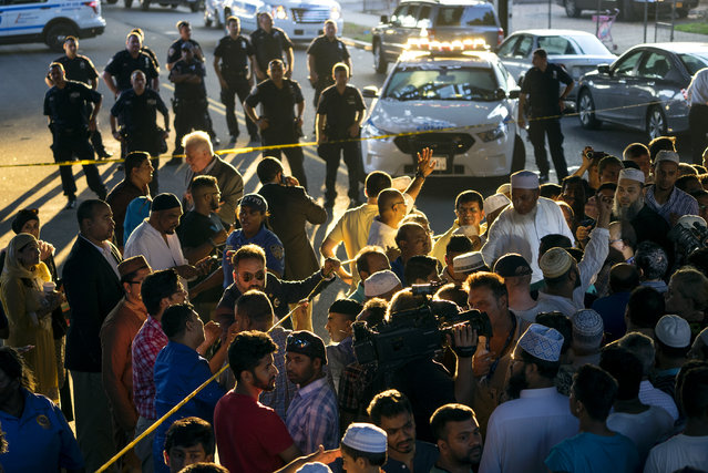 People gather for a demonstration Saturday, August 13, 2016, near a crime scene after an imam and his friend were fatally shot while walking home from a mosque. Police said 55-year-old Imam Maulama Akonjee and his 64-year-old associate, Tharam Uddin, were shot in the back of the head as they left the Al-Furqan Jame Masjid mosque in the Ozone Park section of Queens. (Photo by Craig Ruttle/AP Photo)