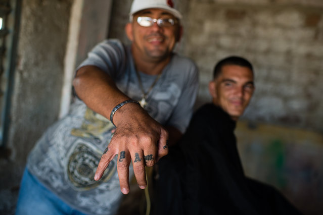 Barber, Debray Alonzo, 47, shows the tattoo of OBAMA on each finger of his right hand. He says he likes the United States and President Obama, so he wanted to have his name tattooed. On the right is Joel Vallero, 26, who is getting a haircut in the small shack in the poor neighborhood of Juruquey, in Camaguey. (Photo by Sarah L. Voisin/The Washington Post)