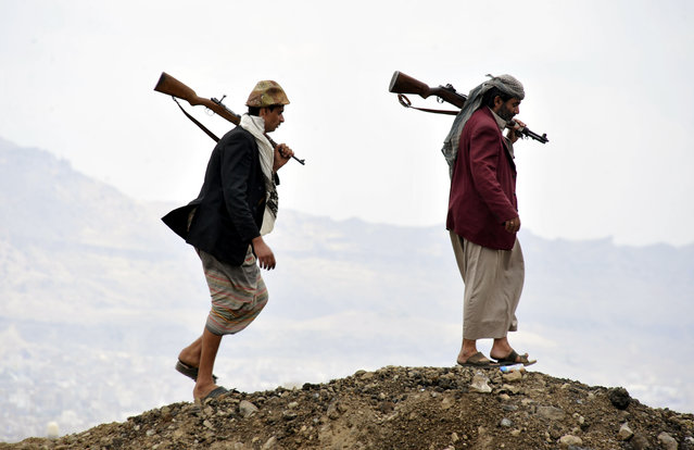 Members of the Shiite rebel militias walk atop a hill at the Al-Iman Sunni Islamic University which they seized control of it in Sana'a, Yemen, 29 September 2014.  Reports state the Shiite Houthi rebel movement still refuses to withdraw its militias from the capital Sana?a a week after the movement and the Yemeni Government signed a UN-brokered peace deal. (Photo by Yahya Arhab/EPA)