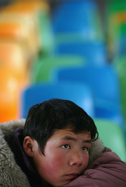 A kid watches TV at an assistance center February 23, 2005 in Shenzhen, Guangdong Province, China. (Photo by Cancan Chu/Getty Images)