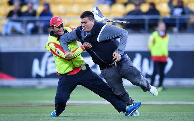 A pitch invader is taken down by security during the Rugby League World Cup quarter- final match between New Zealand and Fiji at Westpac Stadium in Wellington on November 18, 2017. (Photo by Marty Melville/AFP Photo)